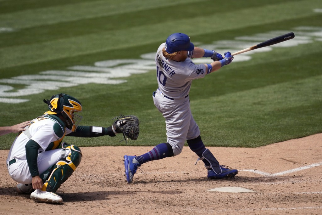 Los Angeles Dodgers' Justin Turner, right, hits a run-scoring double in front of Oakland Athletics catcher Aramis Garcia during the seventh inning of ...