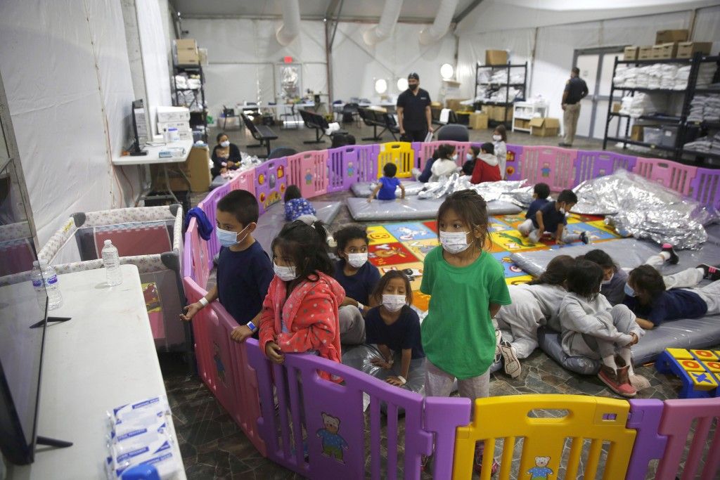 FILE - In this March 30, 2021, file photo, young unaccompanied migrants, from ages 3 to 9, watch television inside a playpen at the U.S. Customs and B...
