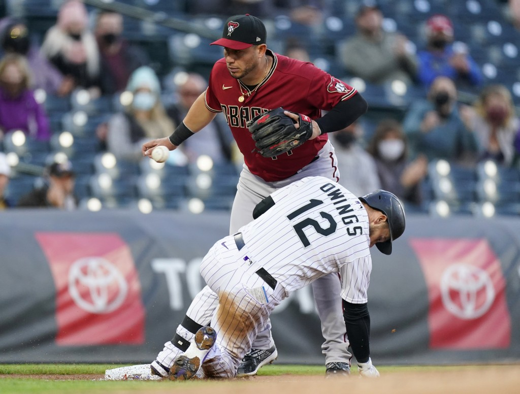 Colorado Rockies' Chris Owings, front, slides safely into third base with an RBI triple as Arizona Diamondbacks third baseman Asdrubal Cabrera fields ...