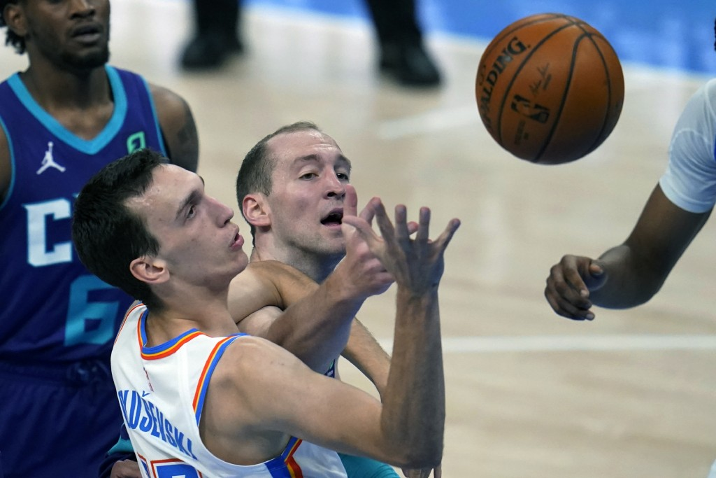 Oklahoma City Thunder forward Aleksej Pokusevski, left, and Charlotte Hornets center Cody Zeller, right, watch a rebound in the first half of an NBA b...