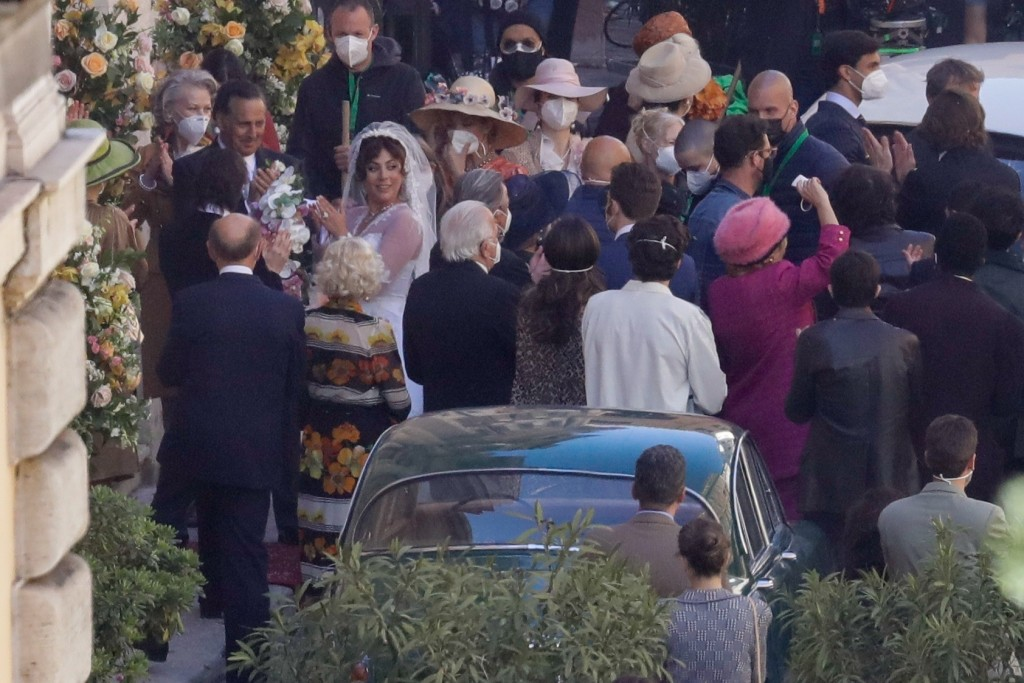 Lady Gaga, wearing a wedding dress in background left, plays Maurizio Gucci's former wife Patrizia Reggiani during the shooting of a movie by Ridley S...