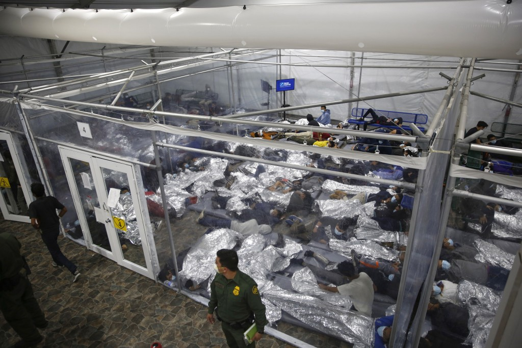 FILE - In this March 30, 2021, file photo, young minors lie inside a pod at the Donna Department of Homeland Security holding facility, the main deten...