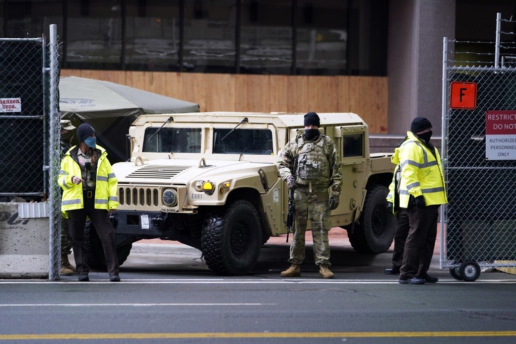 A National Guard soldier, center, stands guard with deputies at the restricted vehicle entrance of the Hennepin County Government Center, Thursday, Ap...