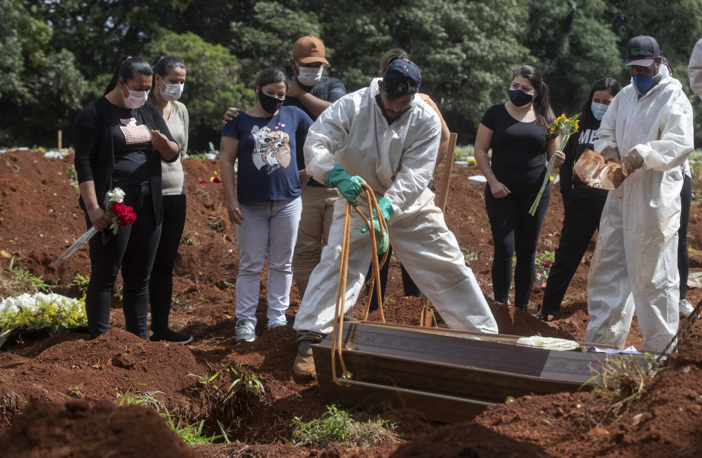 People attend the burial of a relative who died from complications related to COVID-19 at the Vila Formosa cemetery in Sao Paulo, Brazil, Wednesday, A...