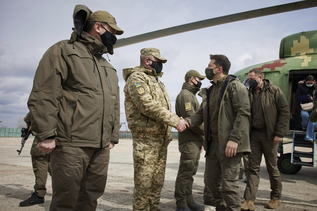 Ukrainian President Volodymyr Zelenskiy shakes hands a soldier as he visits the war-hit Donetsk region, eastern Ukraine, Thursday, April 8, 2021. Ukra...