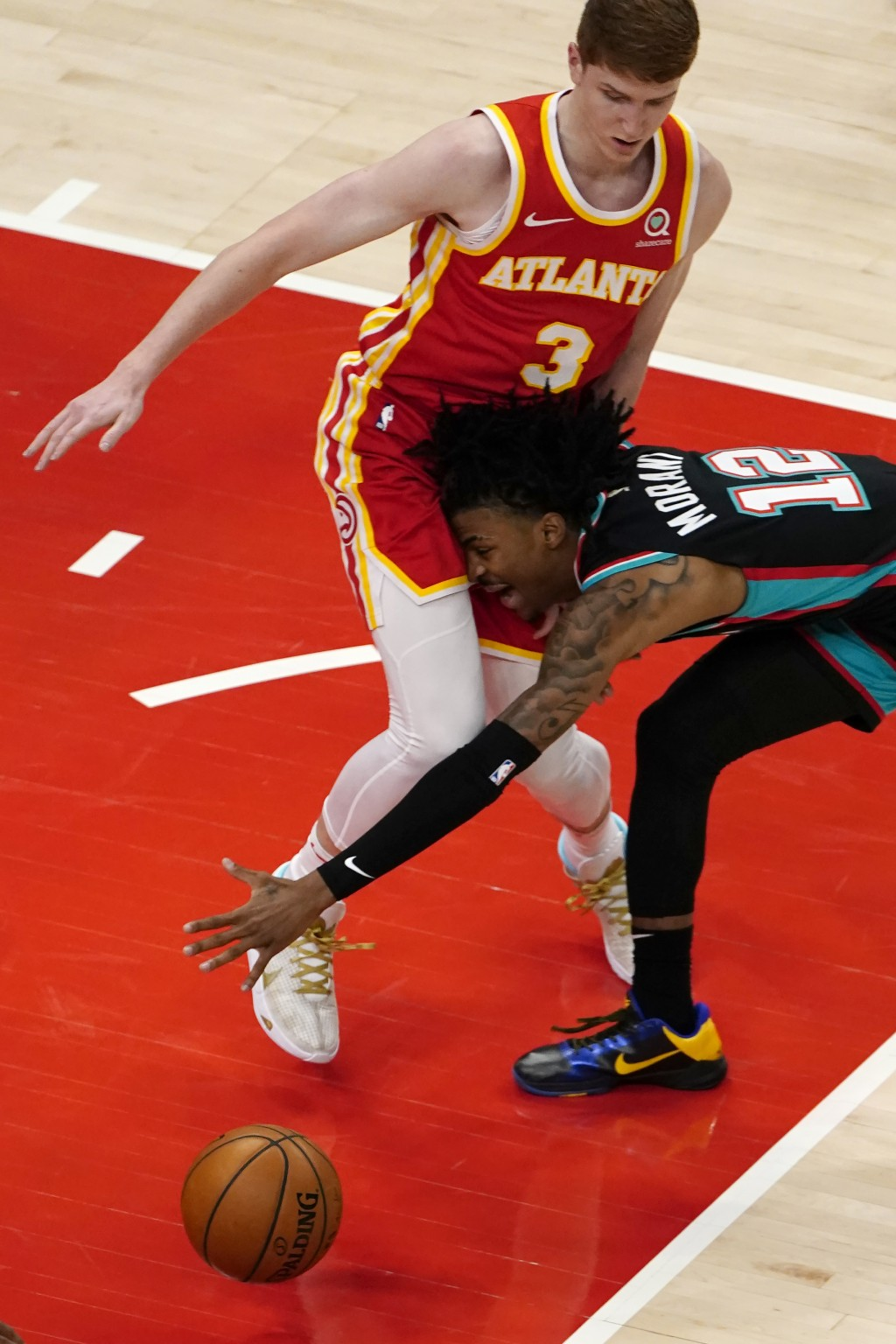 Memphis Grizzlies guard Ja Morant (12) loses control of the ball as he crashes into Atlanta Hawks guard Kevin Huerter (3) in the first half of an NBA ...