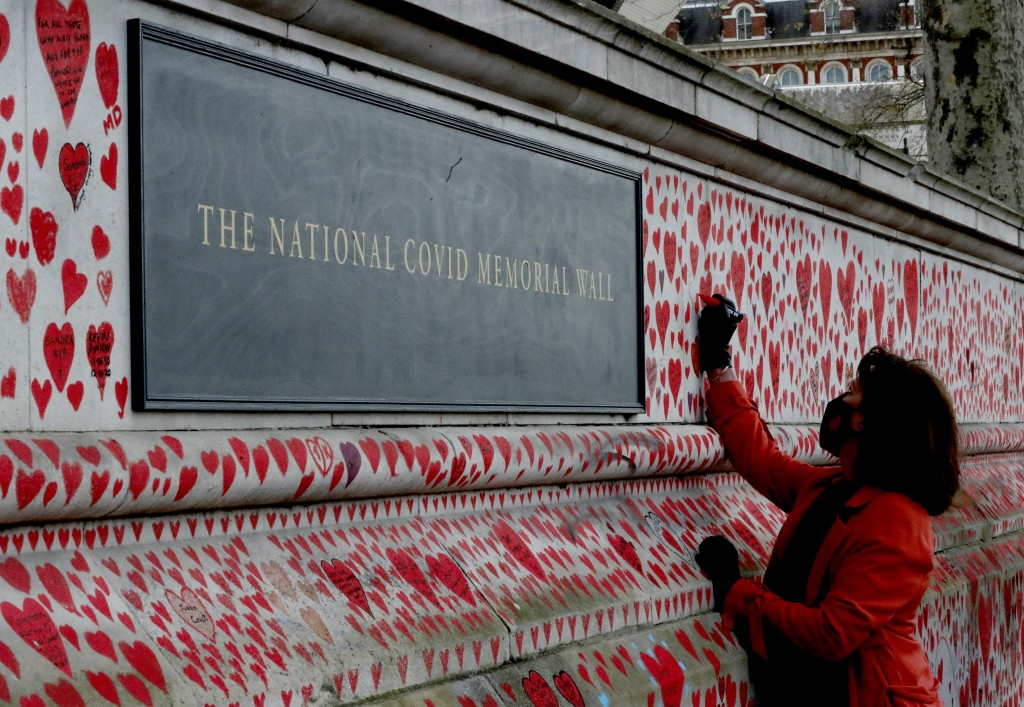 Fran Hall draws one of the last hearts as people paint red hearts to complete the approximately 150,000 hearts being painted onto the National Covid M...