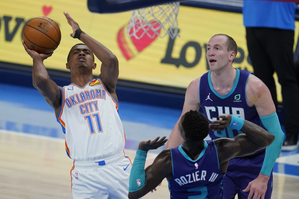 Oklahoma City Thunder guard Theo Maledon (11) shoots in front of Charlotte Hornets guard Terry Rozier (3) and center Cody Zeller, right, in the first ...