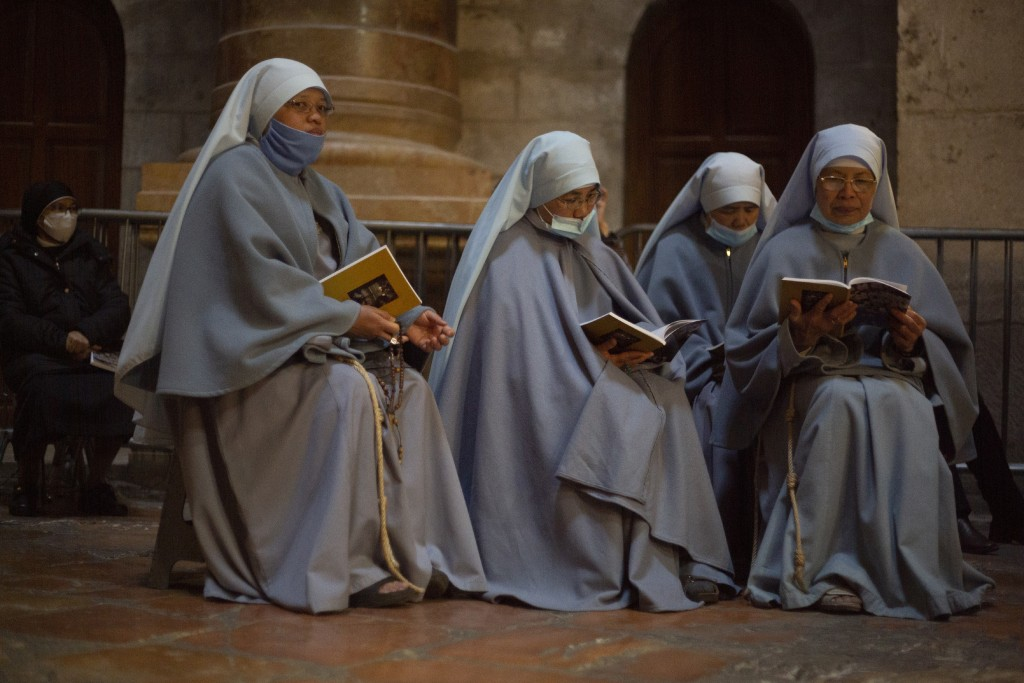 Nuns pray in the Church of the Holy Sepulchre, traditionally where many Christians believe Jesus Christ was crucified, buried and rose from the dead, ...