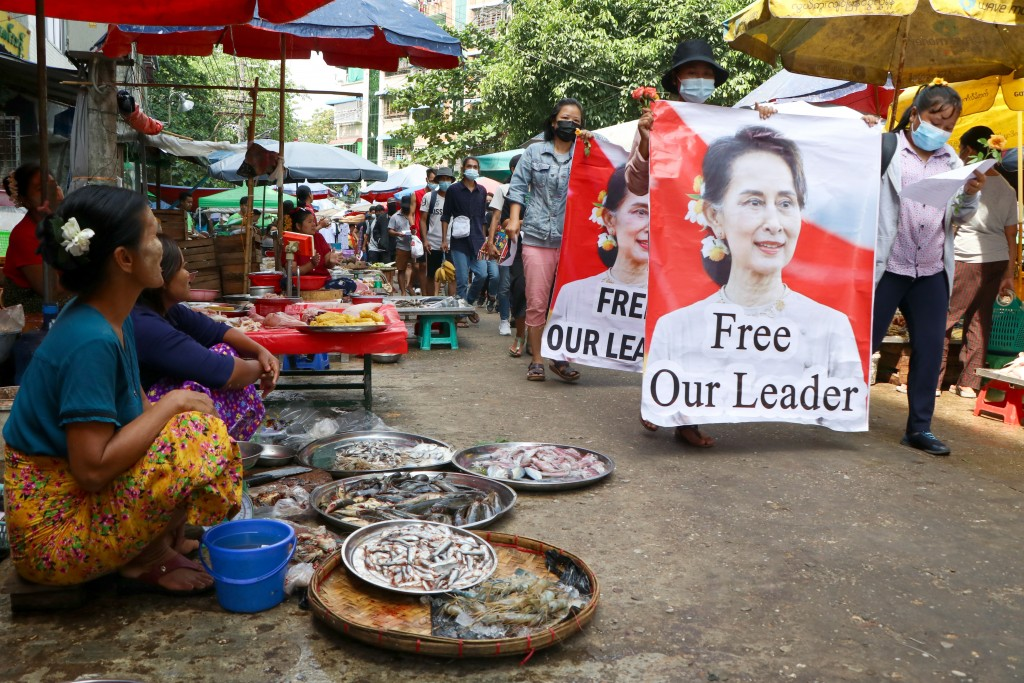 Anti-coup protesters walk through a market with images of ousted Myanmar leader Aung San Suu Kyi at Kamayut township in Yangon, Myanmar Thursday, Apri...