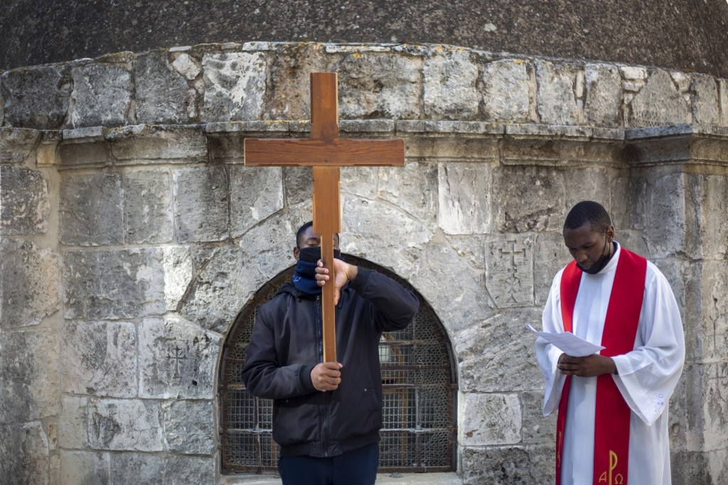 Christians, one carrying a cross, pray during the Good Friday procession after walking in the Via Dolorosa near the Church of the Holy Sepulchre, trad...