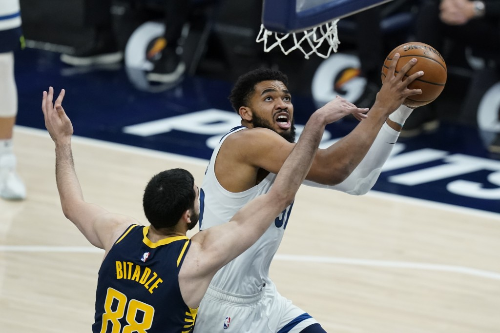 Minnesota Timberwolves' Karl-Anthony Towns (32) is fouled by Indiana Pacers' Goga Bitadze (88) as he goes up for a shot during the first half of an NB...