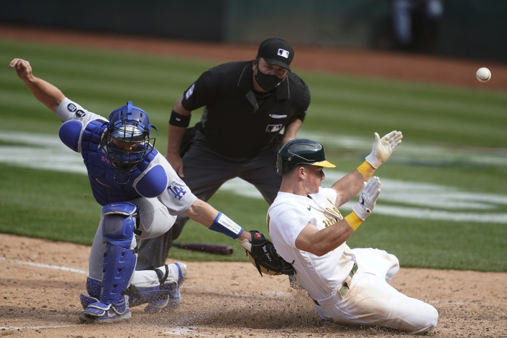 Oakland Athletics' Matt Chapman, right, slides home to score past Los Angeles Dodgers catcher Will Smith during the ninth inning of a baseball game in...