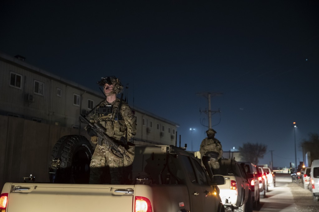 FILE - In this Nov. 28, 2019, file photo armed soldiers stand guard in the motorcade for President Donald Trump speaks during a surprise Thanksgiving ...
