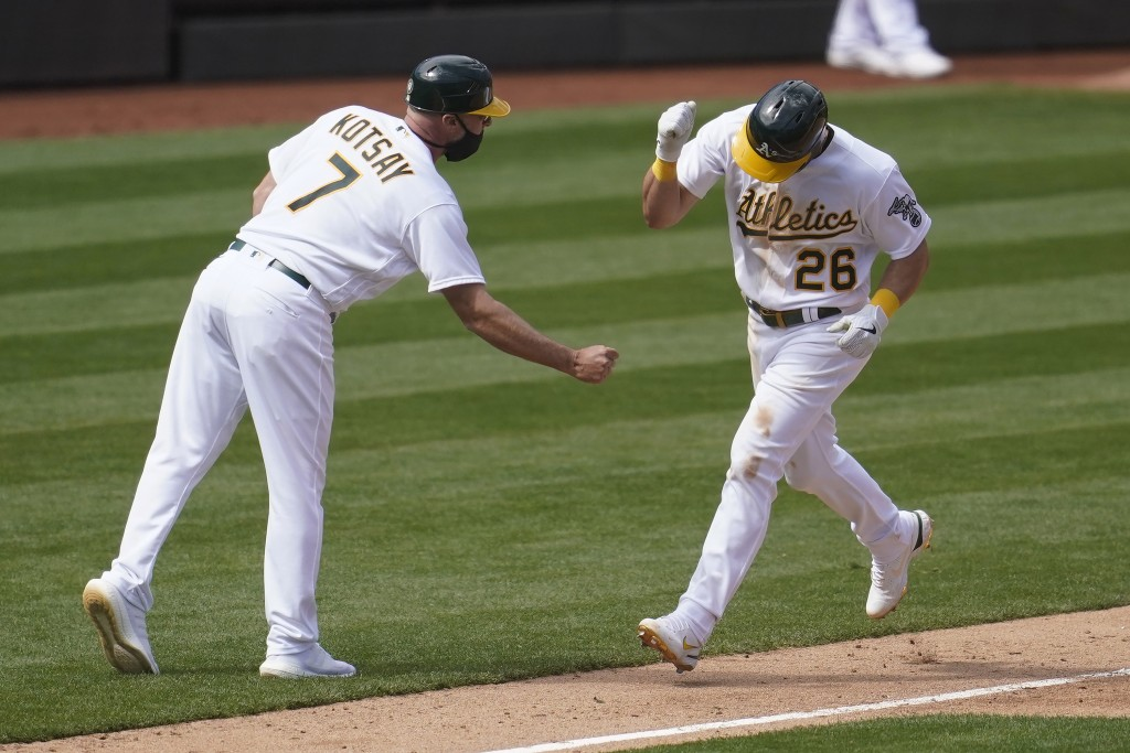 Oakland Athletics' Matt Chapman (26) is congratulated by third base coach Mark Kotsay (7) after hitting a solo home run against the Los Angeles Dodger...