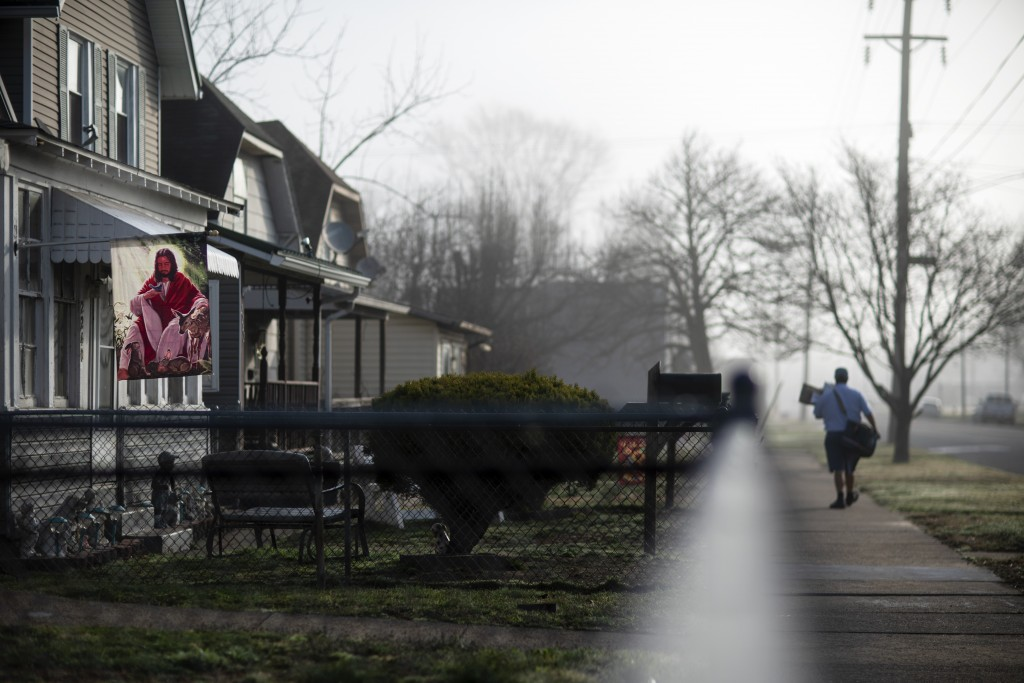 A banner decorated with the image of Jesus hangs outside a home as a mail carrier walks down the street in Huntington, W.Va., Wednesday, March 17, 202...