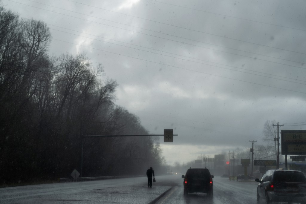 A man walks through a hail storm as the Quick Response Team's vehicle drives to visit another client who recently overdosed, Thursday, March 18, 2021,...