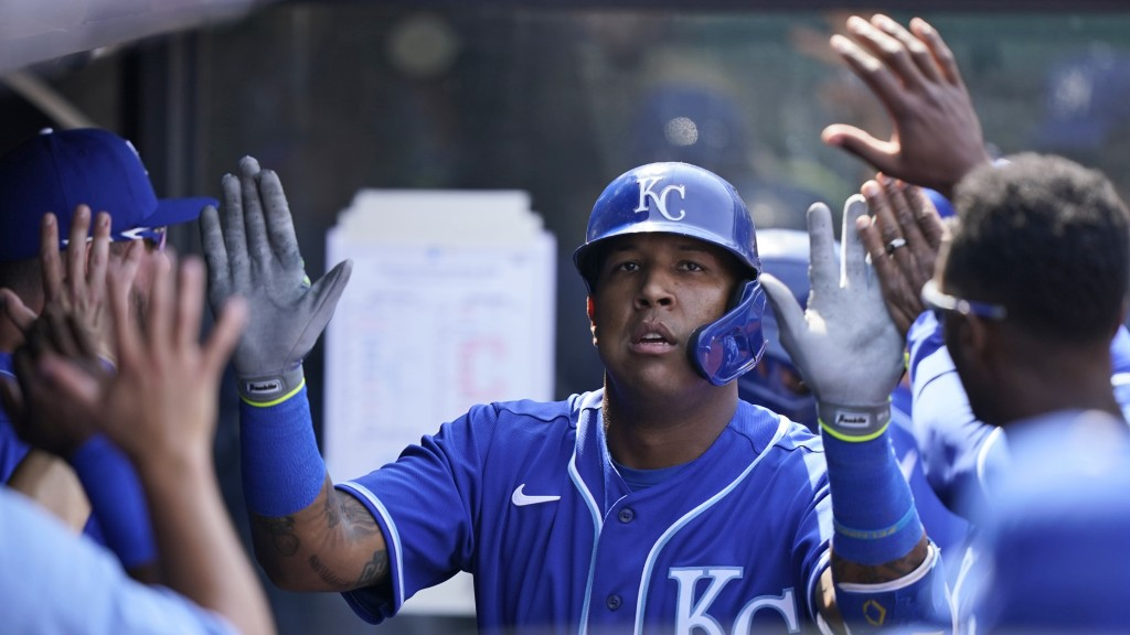 Kansas City Royals' Salvador Perez is congratulated by teammates after hitting a solo home run off Cleveland Indians starting pitcher Shane Bieber in ...