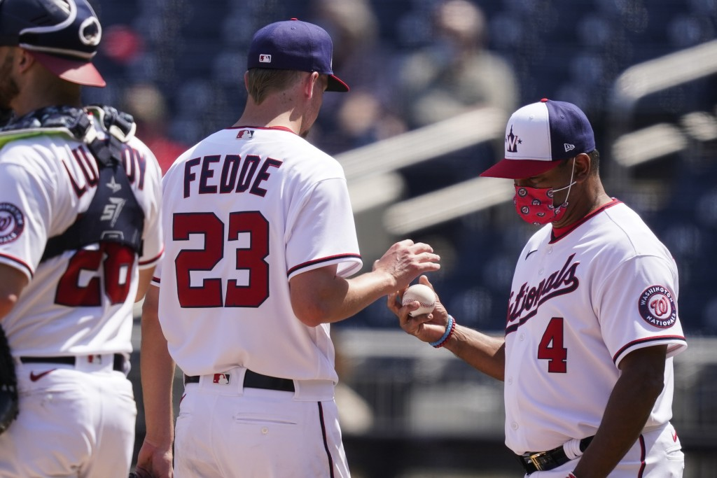 Washington Nationals starting pitcher Erick Fedde is relieved by manager Dave Martinez (4) during the second inning of the first baseball game of a ba...