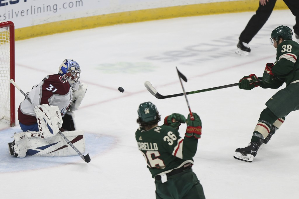 Minnesota Wild's Ryan Hartman (38) shoots the puck at Colorado Avalanche's goalie Philipp Grubauer (31) during the first period of an NHL hockey game ...