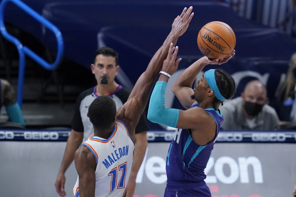 Charlotte Hornets guard Devonte' Graham, right, shoots as Oklahoma City Thunder guard Theo Maledon (11) defends in the first half of an NBA basketball...