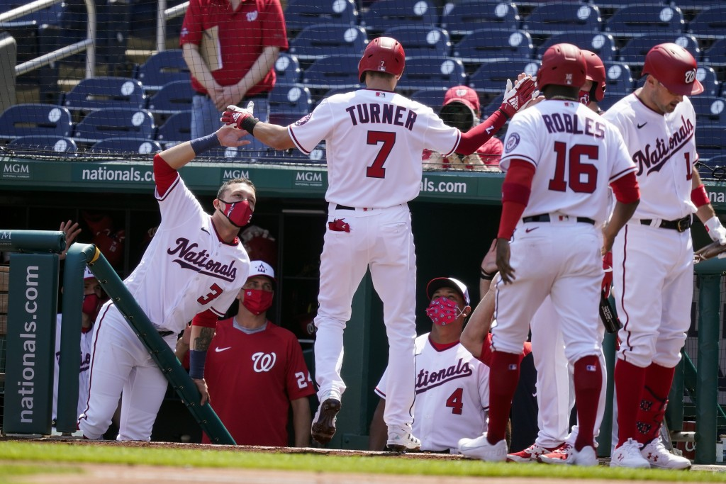 Washington Nationals' Trea Turner celebrates his two-run homer during the first inning in the first baseball game of a doubleheader against the Atlant...