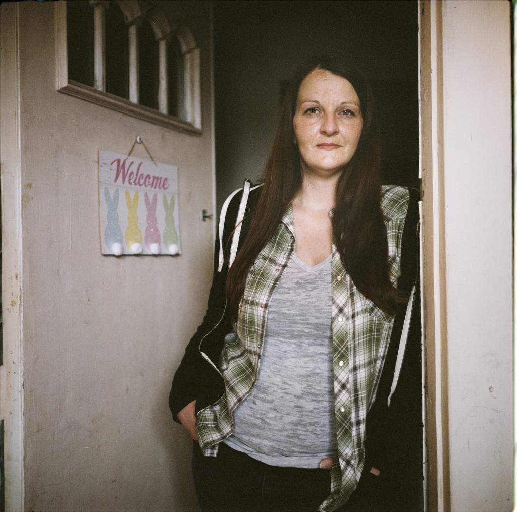 In this photo made with a medium format film camera, Sarah Kelly, 37, stands in the doorway of her home in Guyandotte, W.Va., Wednesday, March 17, 202...