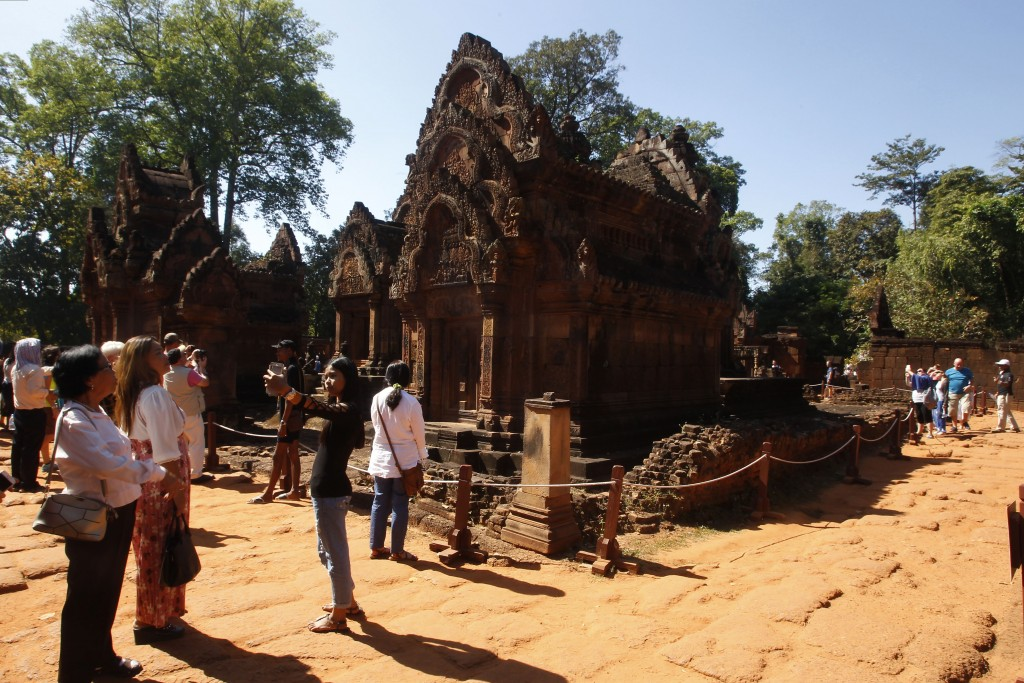 FILE - In this Dec. 23, 2017, file photo, tourists visit Banteay Srey temple outside Siem Reap, Cambodia. Cambodia is closing the Angkor temple comple...