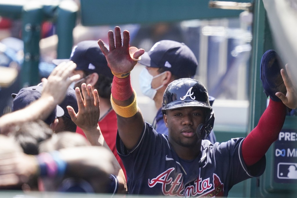 Atlanta Braves' Ronald Acuna Jr. celebrates scoring during the second inning of the first baseball game of a baseball doubleheader against the Washing...
