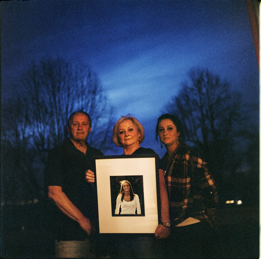 In this photo made with a medium format film camera, Jeff and Lola Carter stand with their daughter, Amanda, and a framed photo of Kayla, their daught...