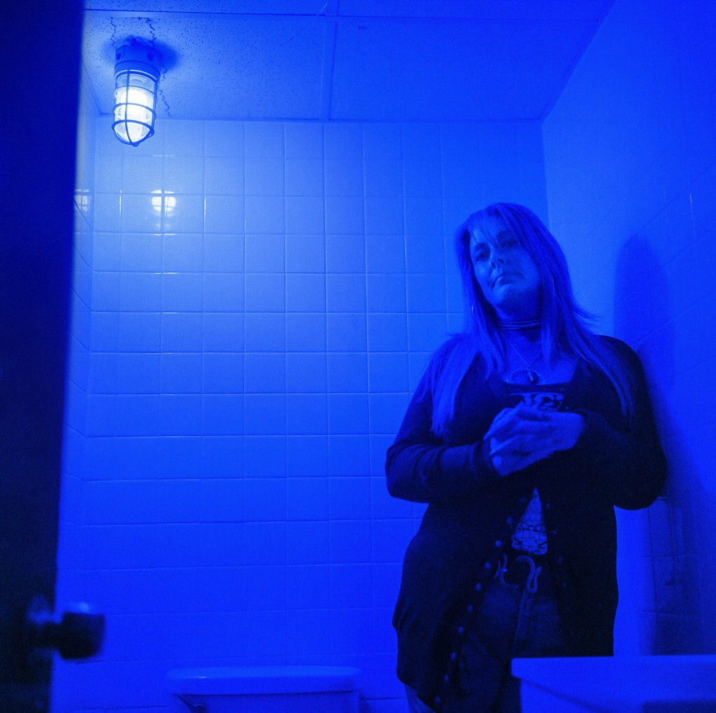 In this photo made with a medium format film camera, Misti Mann-France stands for a portrait in a bathroom at the laundromat she manages under a blue ...