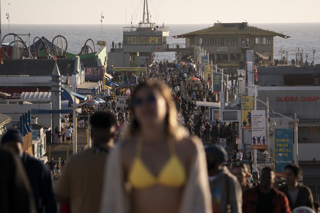 People crowd the Santa Monica Pier in Santa Monica, Calif., Wednesday, April 7, 2021. California Gov. Gavin Newsom announced Tuesday that the state wo...