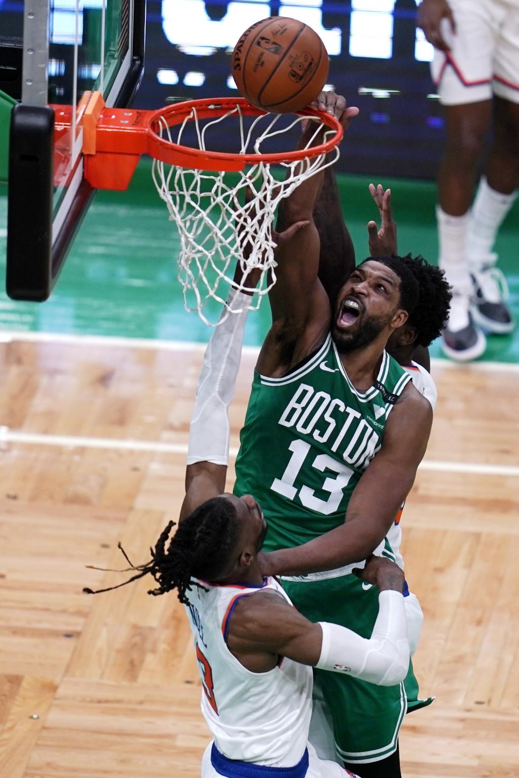Boston Celtics center Tristan Thompson (13) dunks over New York Knicks center Nerlens Noel during the first half of an NBA basketball game Wednesday, ...