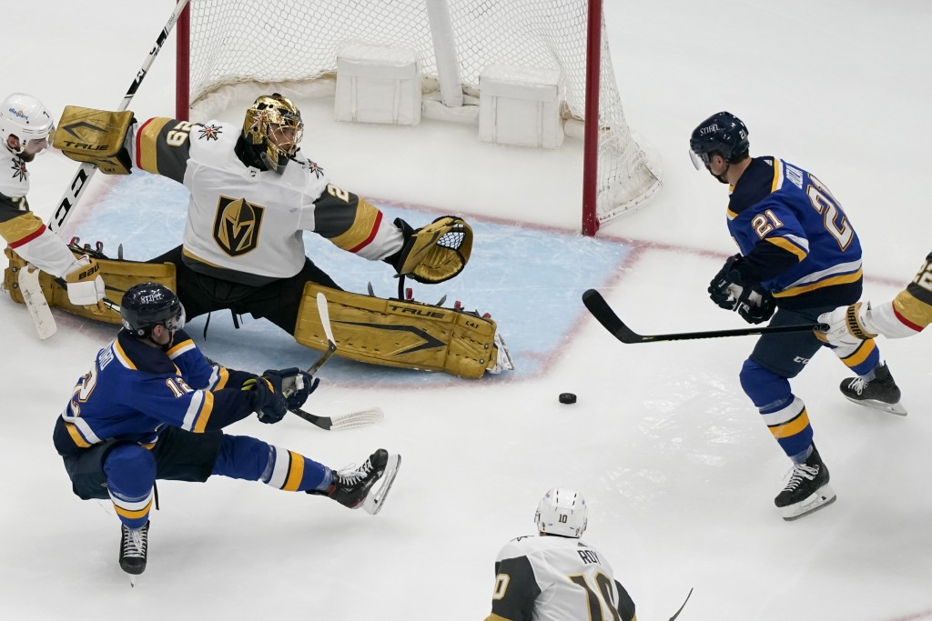 St. Louis Blues' Zach Sanford (12) passes to teammate Tyler Bozak (21) as Vegas Golden Knights goaltender Marc-Andre Fleury (29) defends during the th...