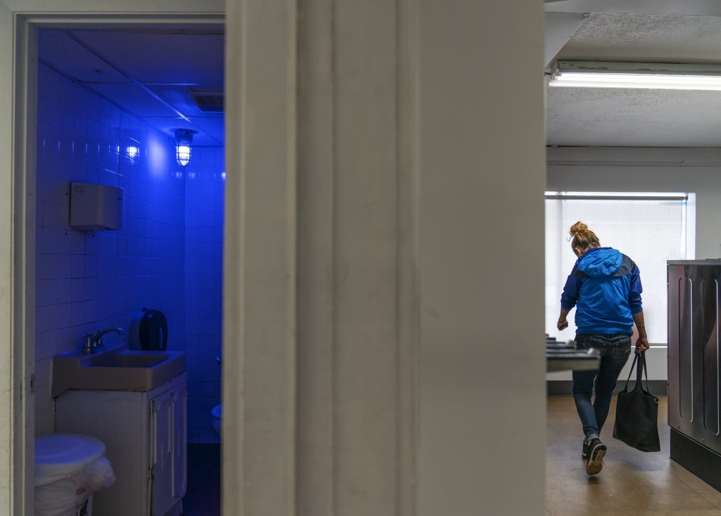 A blue light illuminates the bathroom in the Cookie Carnival laundromat to make it harder for drug users to find a vein in Huntington, W.Va, Thursday,...