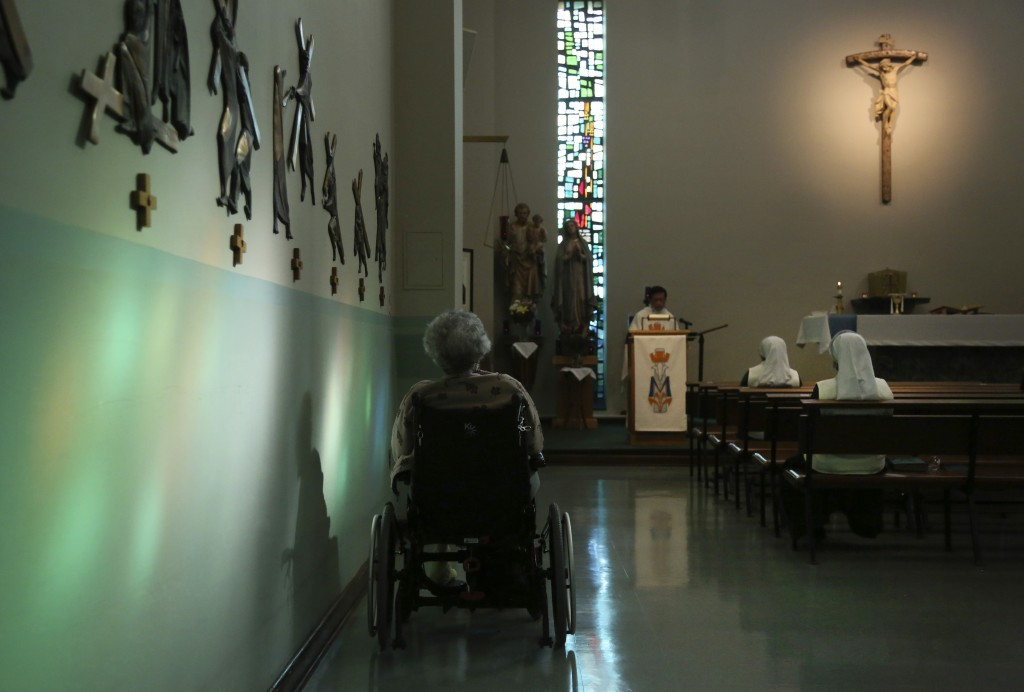 A resident of St. Anne Home sits bathed in sunlight streaming through a stained glass window during morning Mass attended by nuns and residents of the...