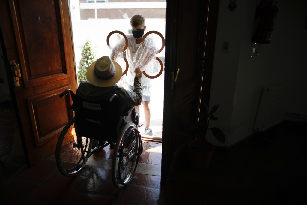 Ramiro Pisani holds the hands of his grandfather Pedro Aberastegui through a plastic sleeve from outside the Reminiscencias residence for the elderly ...