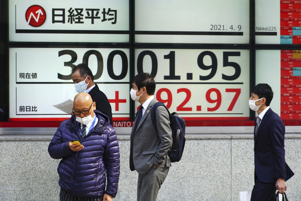 People wearing protective masks stand in front of an electronic stock board showing Japan's Nikkei 225 index at a securities firm in Tokyo Friday, Apr...