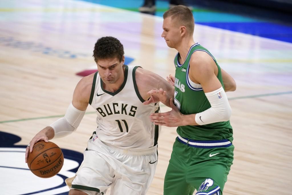 Milwaukee Bucks center Brook Lopez (11) works against Dallas Mavericks center Kristaps Porzingis, right, in the first half of an NBA basketball game i...