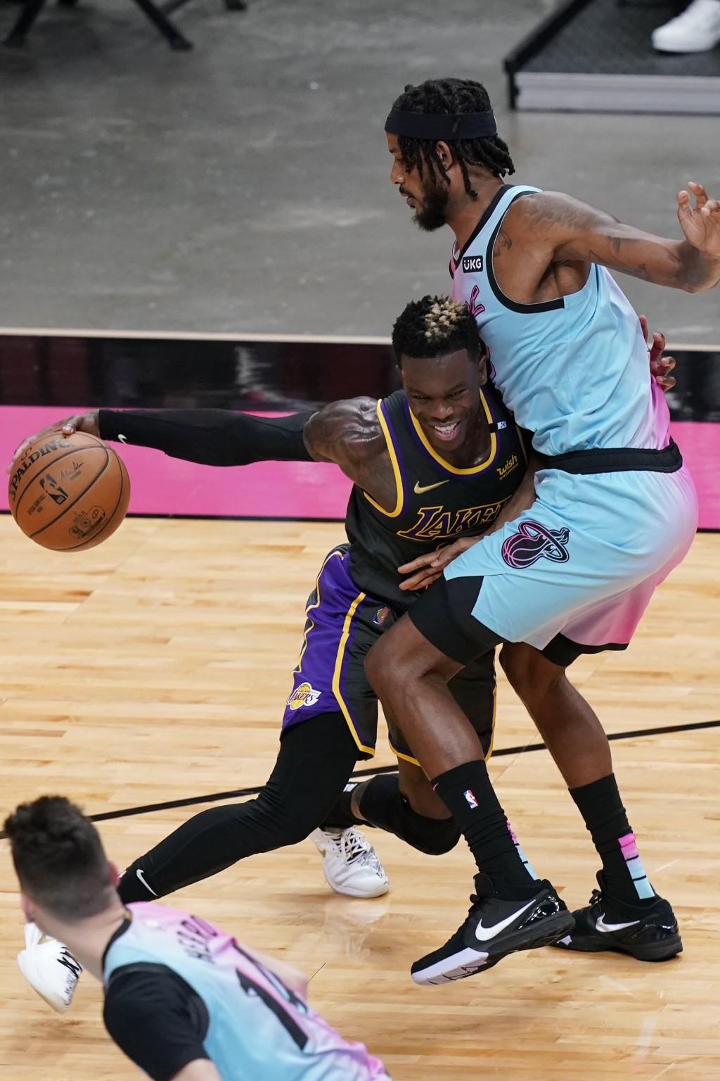 Los Angeles Lakers guard Dennis Schroder (17) tries to dribble around Miami Heat forward Trevor Ariza (8), during the first half of an NBA basketball ...