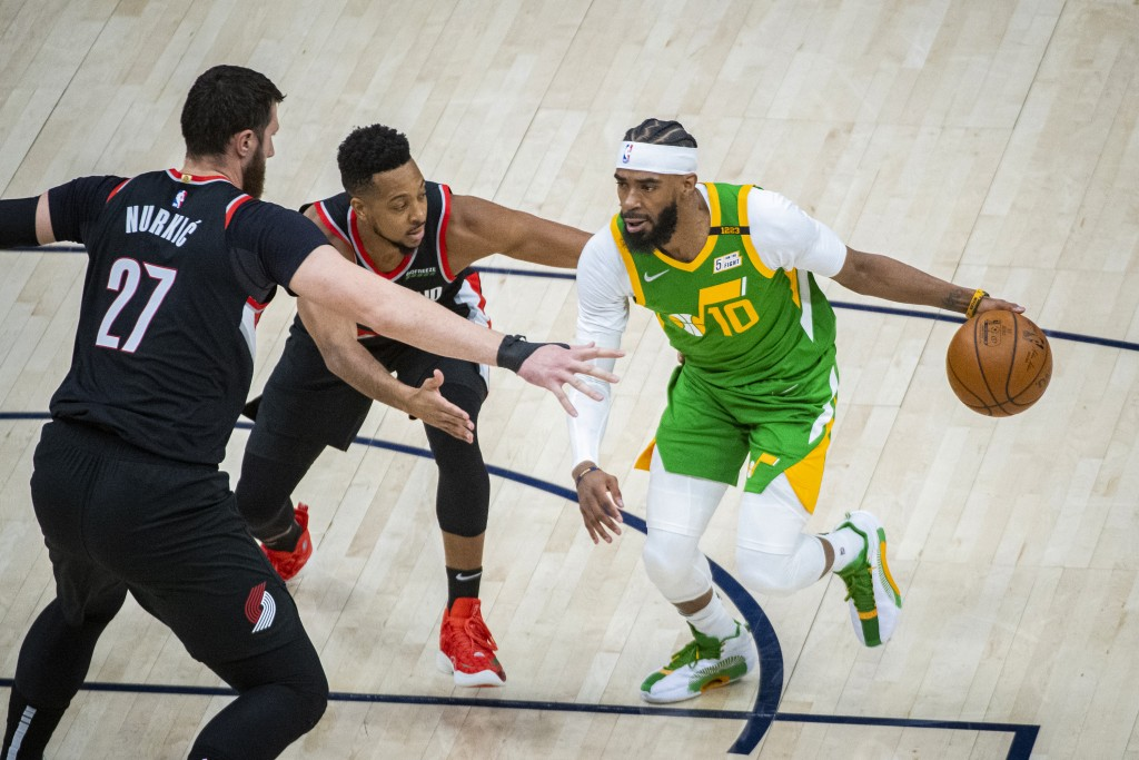 Utah Jazz guard Mike Conley (10) drives the ball on Portland Trail Blazers center Jusuf Nurkic (27) as guard CJ McCollum, rear, also defends during th...