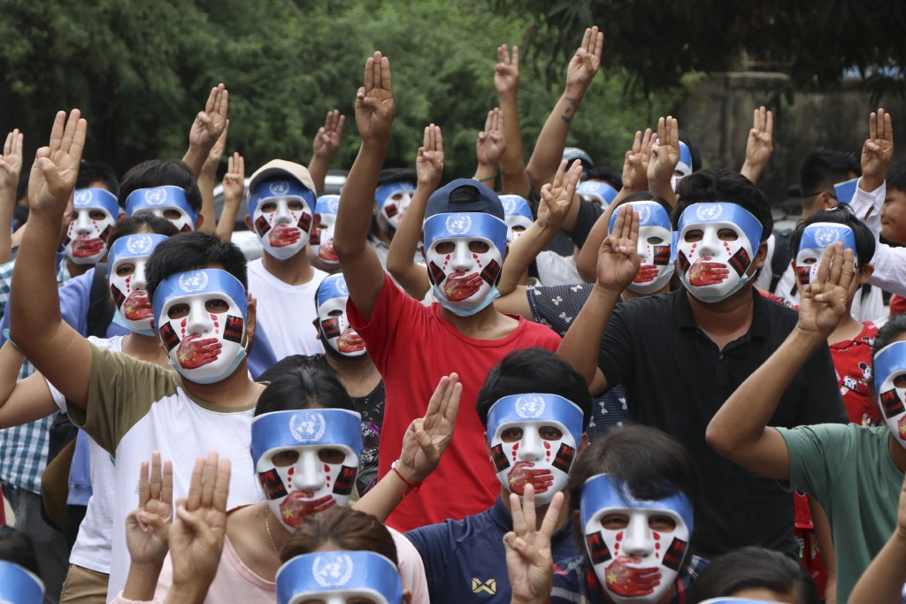 Young demonstrators flash the three-fingered symbol of resistance during an anti-coup mask strike in Yangon, Myanmar, Sunday, April 4, 2021. Threats o...