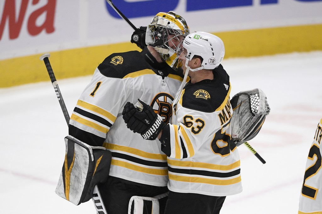 Boston Bruins goaltender Jeremy Swayman (1) and left wing Brad Marchand (63) celebrate after the team's NHL hockey game against the Washington Capital...