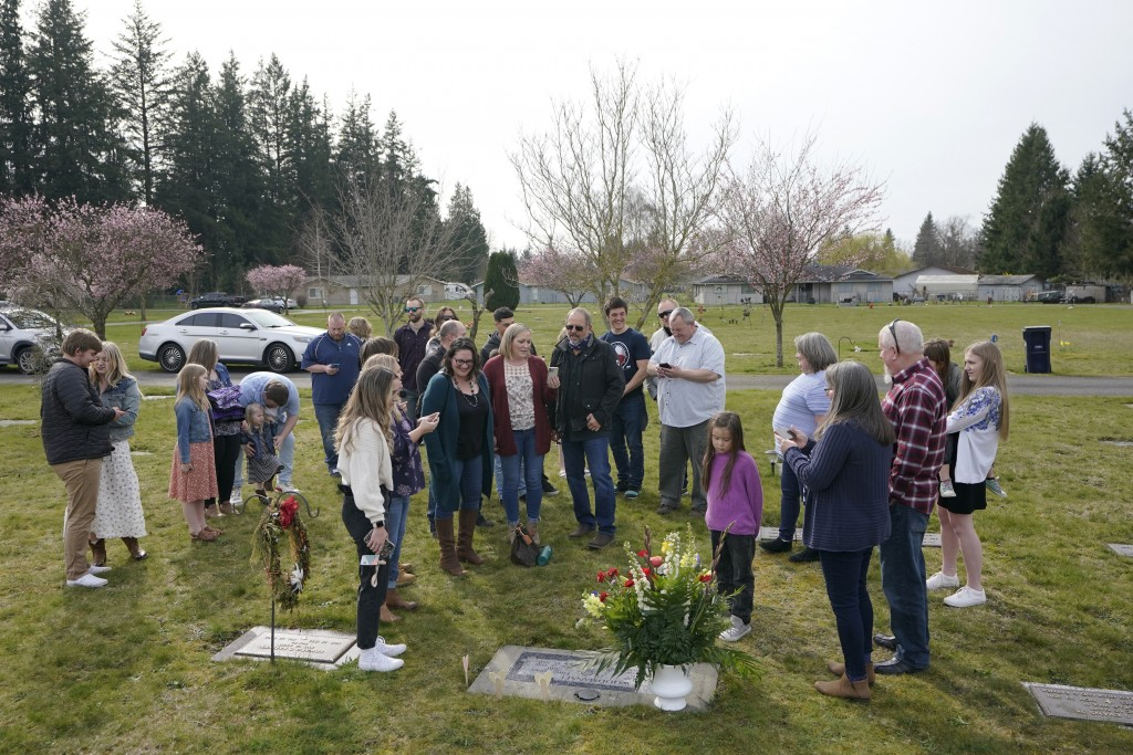 Family members and friends sing as they gather around the headstone Carole Rae Woodmansee shares with her husband Jim (who died in 2003) at Union Ceme...