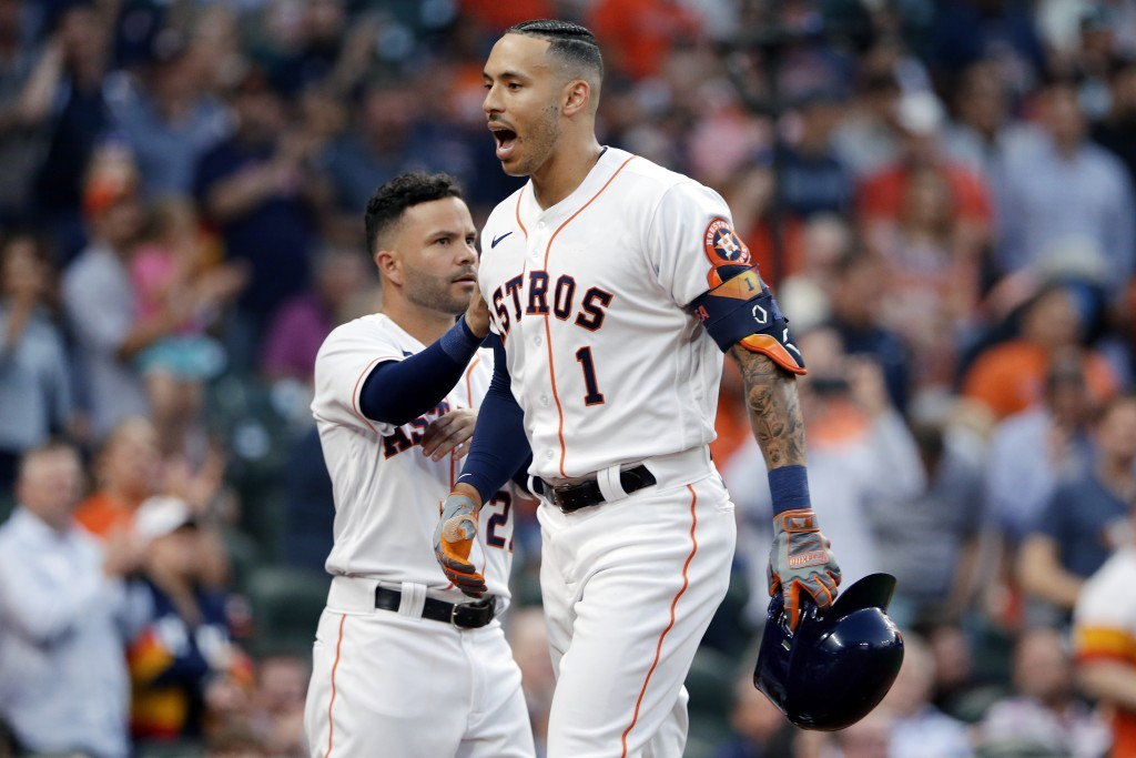 Houston Astros' Jose Altuve, left, pats Carlos Correa (1) as they celebrate Correa's home run during the second inning of a baseball game against the ...