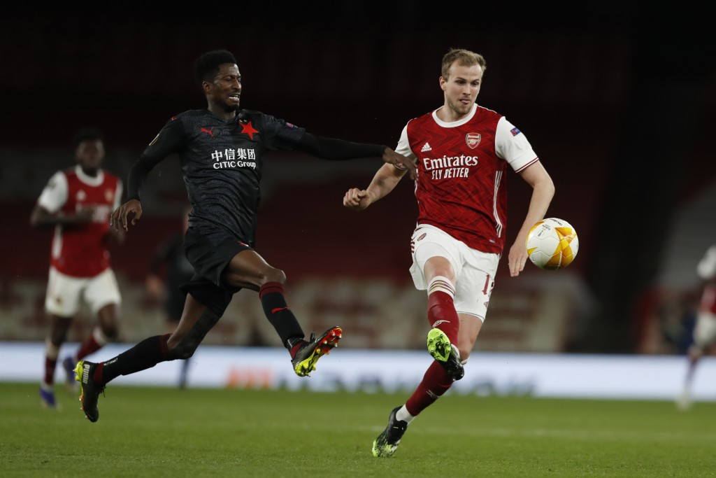 Arsenal's Rob Holding, right, passes the ball as Slavia Prague's Peter Olayinka tries to sop him during the Europa League quarterfinal soccer match be...