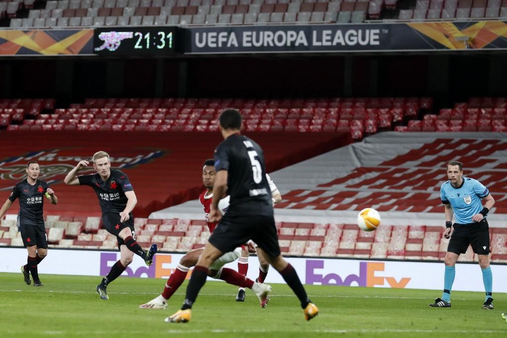 Slavia Prague's Petr Sevcik, left, takes a shot during the Europa League quarterfinal soccer match between Arsenal and Slavia Prague at Emirates stadi...
