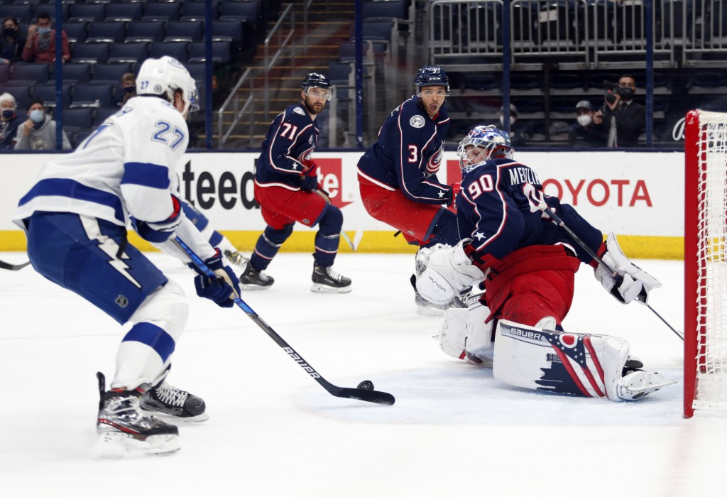 Tampa Bay Lightning defenseman Ryan McDonagh, left, shoots and scores against Columbus Blue Jackets goalie Elvis Merzlikins, right, during the first p...