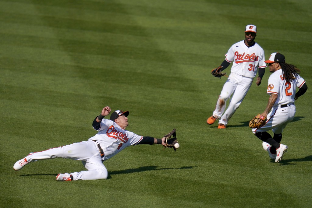 Baltimore Orioles left fielder Ryan Mountcastle, left, attempts a diving catch on a ball hit by Boston Red Sox's Christian Vazquez during the sixth in...