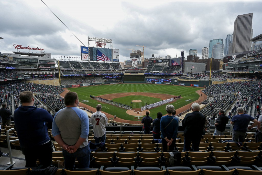 The Seattle Mariners and Minnesota Twins stand along the baselines and fans stand for the national anthem for the home opener baseball game at Target ...